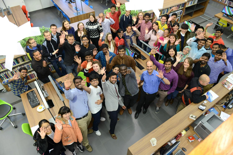 grupa studentów z różnych krajów radośnie macha do kamery