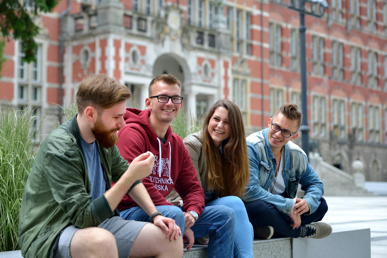 radosna grupa znajomych rozmawia na ławce przed budynkiem Politechniki