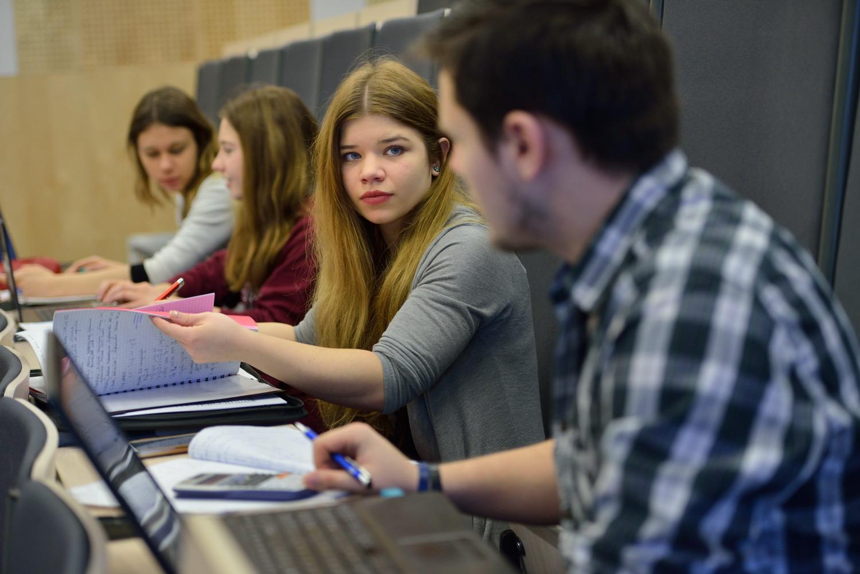 studenci na sali wykładowej liczą i robią notatki z zajęć